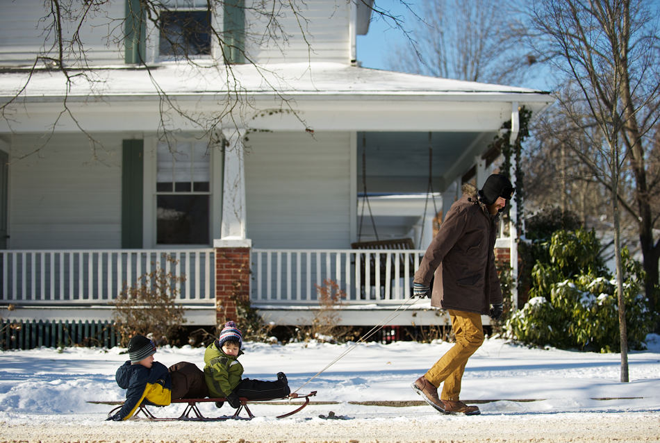 Paul Knight pulls his sons Ashton, left, 4, and Logan, 2, on a sled as they return home  on Wednesday, Jan.  22, 2014 in Fredericksburg, Va.   A winter snow left the area with a coating of snow and sub-zero wind chills. (AP Photo/The Free Lance-Star, Dave Ellis)