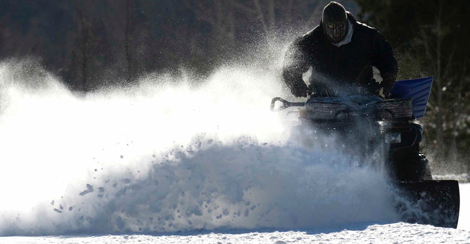Darrell Cooper, a deacon at Hull's Memorial Baptist Church, uses an ATV and a blade to clear the parking lot, Wednesday, Jan. 22, 2014. Following a blanketing snowstorm the day and night before, Fredericksburg area residents dealt with frigid air and wind chill temperatures. (AP Photo/The Free Lance-Star, Reza A. Marvashti)