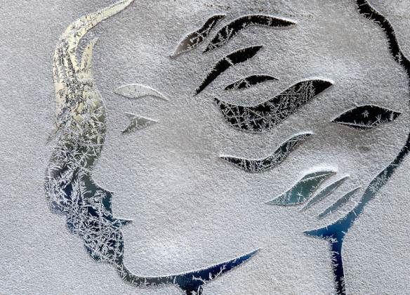 FRED ZWICKY/JOURNAL STAR Ice crystals skate across the surface of a dancing figure etched into the front glass doors of the Madison Theater on January 21 as temperatures dropped nearly below zero with a new blast of winter chill in the Peoria area.