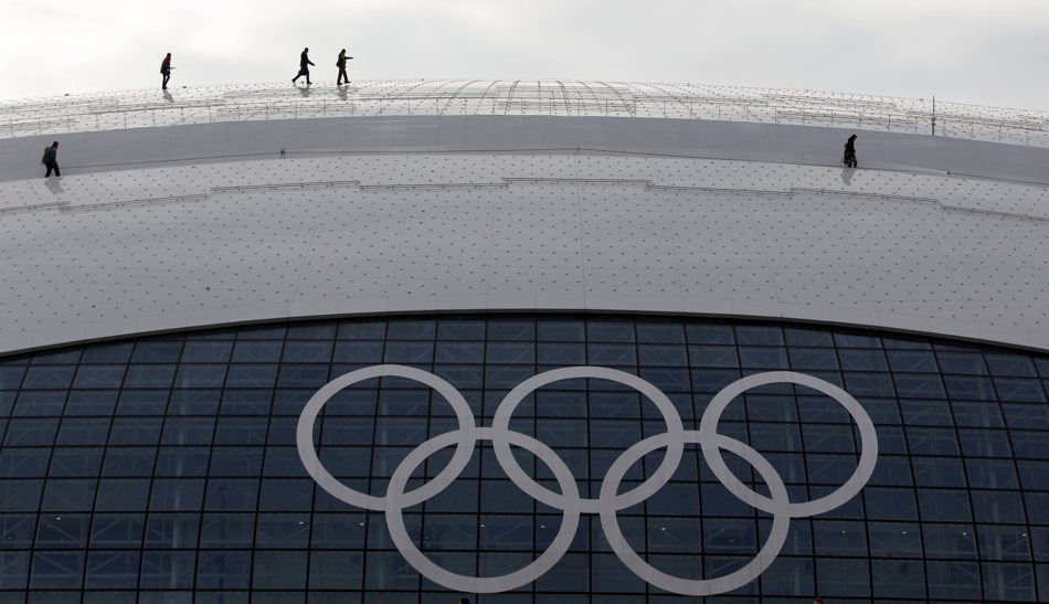 Workers walk across the rooftop of the Bolshoy Ice Dome, site of the ice hockey competitions, ahead of the 2014 Winter Olympics, Tuesday, Feb. 4, 2014, in Sochi, Russia. (AP Photo/Petr David Josek)