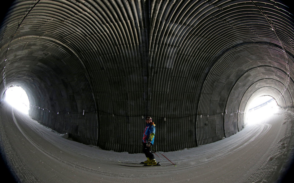 An Olympic worker skis through a tunnel on the way to the Alpine ski course ahead of the 2014 Sochi Winter Olympics, Tuesday, Feb. 4, 2014, in Krasnaya Polyana, Russia. (AP Photo/Charles Krupa)