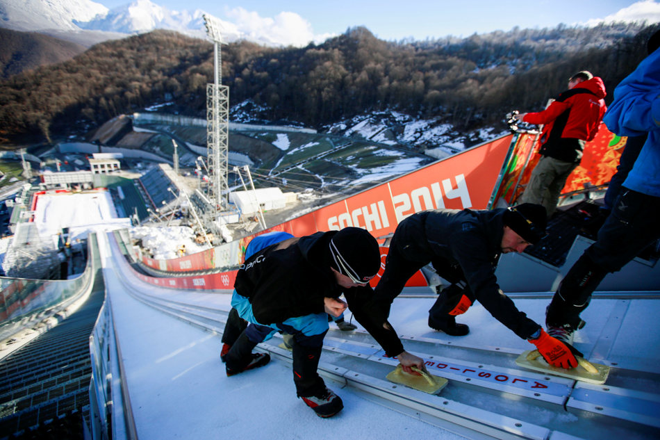 Specialists from Slovenia prepare the ski tracks of the ski jump slope of the large hill at the RusSki Gorki Jumping Center of the Sochi 2014 Winter Olympics, Saturday, Feb. 1, 2014, in Krasnaya Polyana, Russia, where the snow and sliding sports venues for the 2014 Winter Olympics are located. (AP Photo/Gero Breloer)