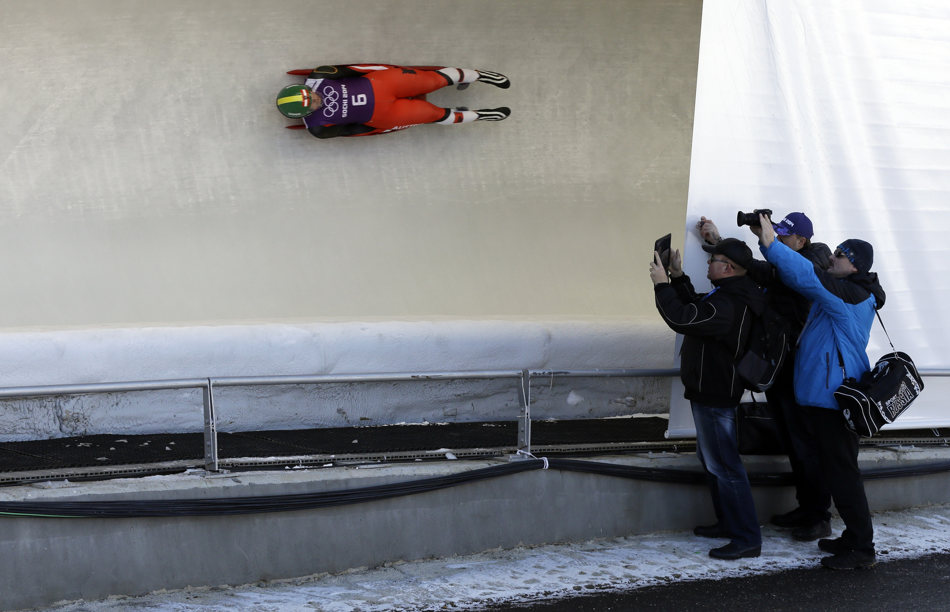 Members of the Russian team photograph Nina Reithmayer of Austria during a training run at the 2014 Winter Olympics, Tuesday, Feb. 4, 2014, in Krasnaya Polyana, Russia. (AP Photo/Natacha Pisarenko)