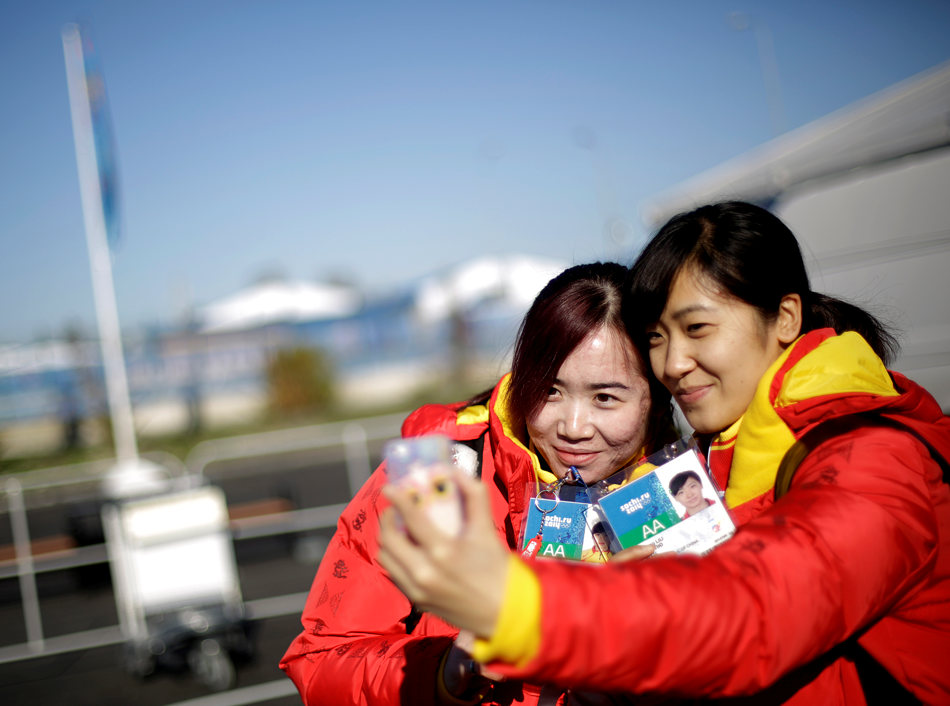 China short track speed skaters Qiuhong Liu, right, and Xue Kong, take a self portrait with a mobile phone upon arriving at the Coastal Cluster athlete's village at the 2014 Winter Olympics, Monday, Feb. 3, 2014, in Sochi, Russia. (AP Photo/David Goldman)