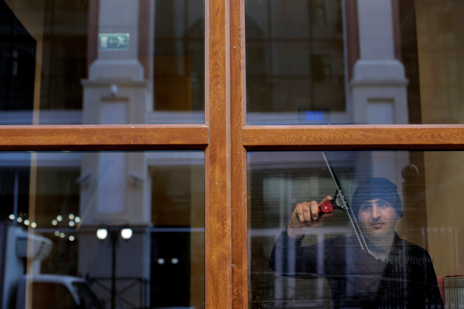 A worker cleans the window of a hotel at Gorki Plaza prior to the 2014 Winter Olympics, Tuesday, Feb. 4, 2014, in Krasnaya Polyana, Russia. The games run from Feb. 7-23.  (AP Photo/Jae C. Hong)