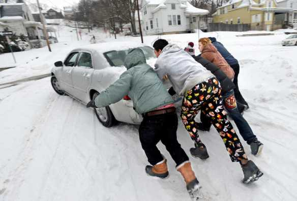 DAVID ZALAZNIK/JOURNAL STAR  A group of passersby jump in to help push a car driven by Ashley Hayes on Monday, Feb. 17 after she became stuck in the street at the intersection of Caroline Street and Glendale Avenue in Peoria.