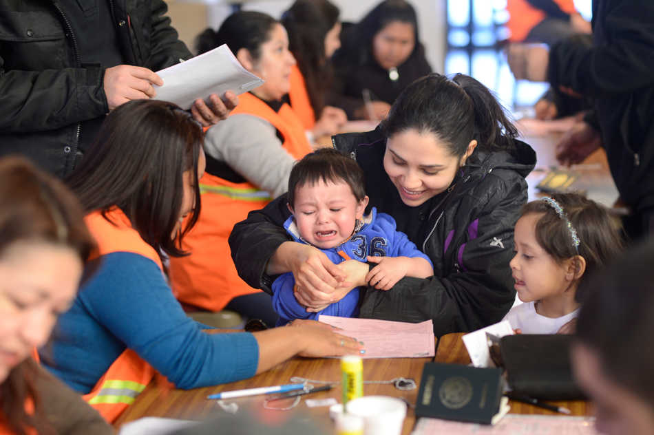 DAVID ZALAZNIK/JOURNAL STAR  Erika Garcia helps her reluctant son Alvaro,1, get his fingerprints taken Friday, Feb. 7 at First United Methodist Church in Peoria where the Chicago Mexican Consulate mobile unit was set up to help hundreds of Mexican nationals who would otherwise need to travel to the consulate in Chicago, process passports and identification applications.