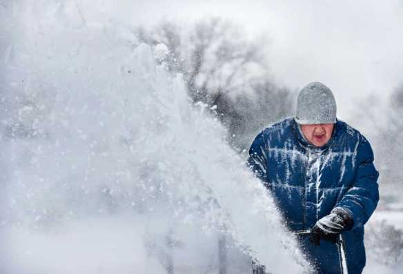 FRED ZWICKY/JOURNAL STAR Retired Rev. Jeff Thompson battles through some blow-back as he clears snow from his driveway on Wednesday, Feb. 5 in Pekin. Thompson, who got help from two of his grandkids, said he also clears the drives of two elderly neighbor ladies as well.