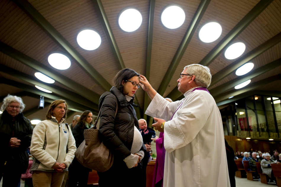 Rev. Valentine Bradley places ashes on expectant mother Sara Cremonesi during Mass at Our Lady of Victory Catholic Church, Wednesday, March 5, 2014, in State College, Pa. Ash Wednesday marks the beginning of the Lenten season, a time when Christians commit to acts of penitence and prayer in preparation for Easter Sunday. (AP Photo/Centre Daily Times, Nabil K. Mark) MANDATORY CREDIT; MAGS OUT