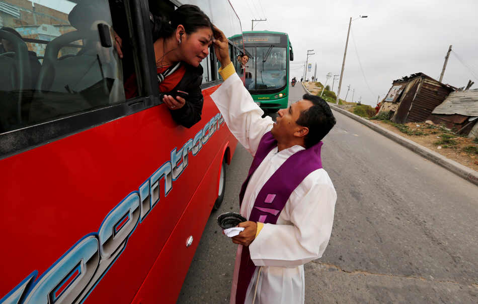 Catholic priest Jesus Cardona places ashes in the shape of a cross on the forehead of a woman traveling by bus in Bogota, Colombia, Wednesday, March 5, 2014. Cardona, 39, walked through the neighborhood of his church the morning of Ash Wednesday to offer blessings to commuters on the start of the Lent, a season of prayer and fasting before Easter. (AP Photo/Fernando Vergara)