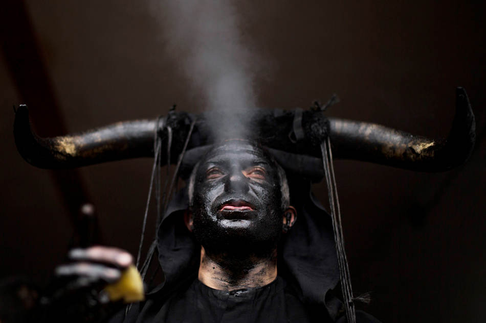A man, covered in oil and soot carrying bull horns on his head and cowbells on a belt representing the devil, blows out smoke in the small village of Luzon, Spain, Saturday, March 1, 2014. Preserved records from the 14th century document Luzon's carnival, but the real origin of the tradition could be much older. Carnival festivals are celebrated in their own way around hundreds of villages in Spain. (AP Photo/Andres Kudacki)