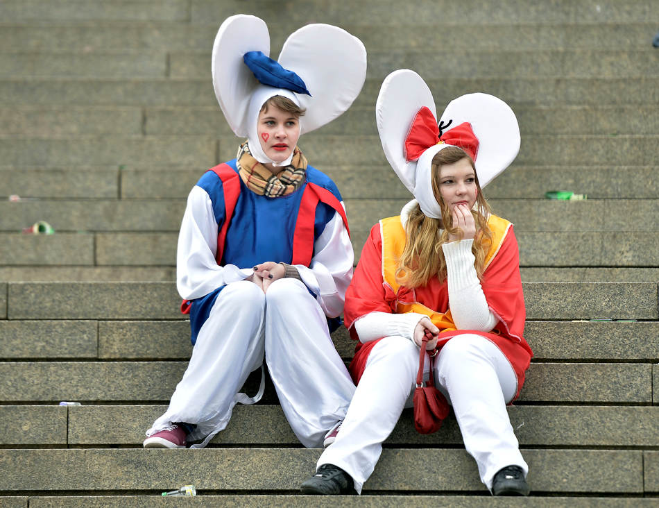 "Two girls waiting on stairs in a street when tens of thousands of revelers dressed in carnival costumes celebrate the start of the street-carnival on the so called ""Old Women's Day"" in the party capital Cologne, Germany, Thursday, Feb. 27, 2014. (AP Photo/Martin Meissner)"