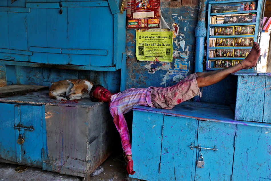 A man smeared in colored powder rests beside a dog in front of closed shops after celebrations marking Holi, the Hindu festival of colors, in Allahabad, India, Monday, March 17, 2014. The holiday, celebrated mainly in India and Nepal, marks the beginning of spring and the triumph of good over evil. (AP Photo/Rajesh Kumar Singh)