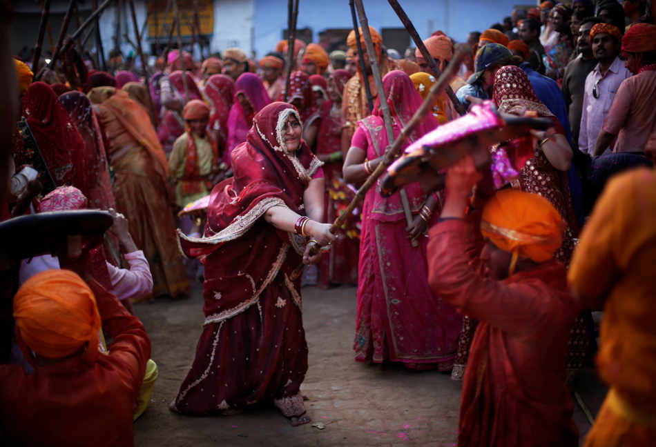 Indian Hindu women from Nandgaon village beat the shield of a man from Barsana village during Lathmar Holi festival at Nandgaon 120 kilometers (75 miles) south of New Delhi, India, Monday, March 10, 2014. According to a tradition which has its roots in Hindu mythology, men from nearby Barsana village are soaked in colored water by men and beaten with sticks by women as they arrive at Nandgaon, believed to be Lord Krishna's village. (AP Photo/Altaf Qadri)
