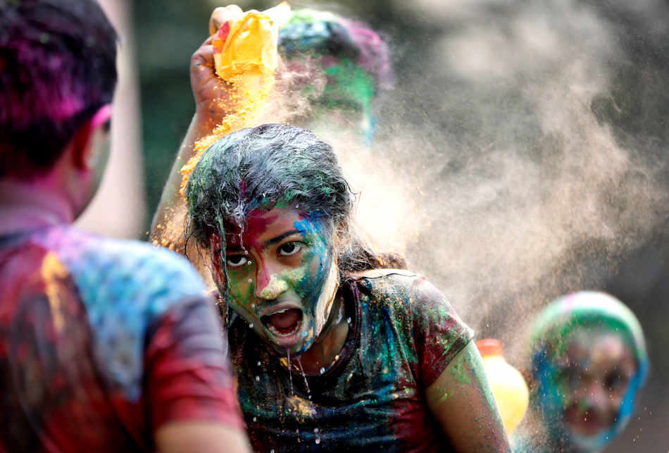 A man throws colored powder on a woman during celebrations marking Holi, the Hindu festival of colors, in Mumbai, India, Monday, March 17, 2014. The holiday, celebrated mainly in India and Nepal, marks the beginning of spring and the triumph of good over evil. (AP Photo/Rajanish Kakade)
