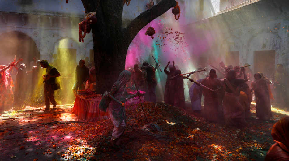 Indian Hindu widows play with colored water for the first time as a part of Holi celebrations organized by the NGO Sulabh at the Meera Sahbhagini Ashram in Vrindavan, India, Friday, March 14, 2014. The widows, many of whom at times have lived desperate lives in the streets of the temple town, celebrated the festival at the century old ashram. After their husband's deaths the women have been banished by their families to the town where devotees believe Lord Krishna was born, for supposedly bringing bad luck. (AP Photo /Manish Swarup)