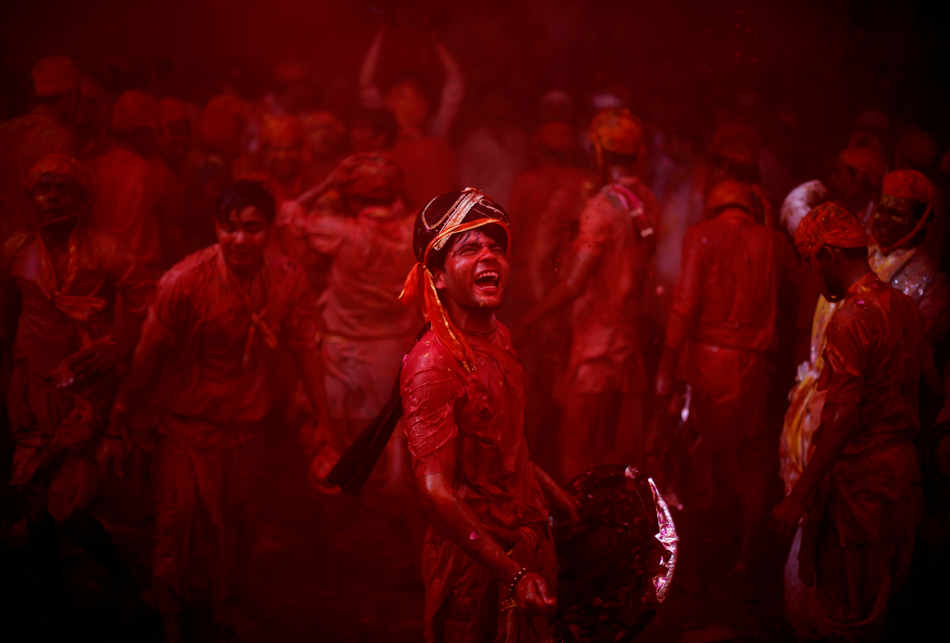 A Hindu man from the village of Nangaon teases men from Barsana as they play holi at the Ladali or Radha temple before the procession for the Lathmar Holi festival, the legendary hometown of Radha, consort of Hindu God Krishna, in Barsana 115 kilometers ( 71 miles) from New Delhi, India, Sunday, March 9, 2014. During Lathmar Holi the women of Barsana beat the men from Nandgaon, the hometown of Krishna, with wooden sticks in response to their teasing as they depart the town. (AP Photo/Altaf Qadri)