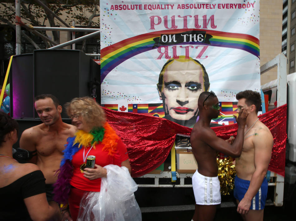Participants in the annual gay and lesbian Mardi Gras parade prepare for the event in front of a banner mocking Russian President Vladimir Putin in Sydney, Saturday, March 1, 2014. Ten Thousand marchers along with 144 floats are entered in the 36th parade. (AP Photo/Rick Rycroft)