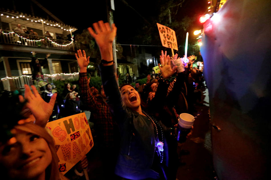 Parade-goers cheer for beads and trinkets during in the Krewe of Muses Mardi Gras parade in New Orleans, Thursday, Feb. 27, 2014. (AP Photo/Gerald Herbert)