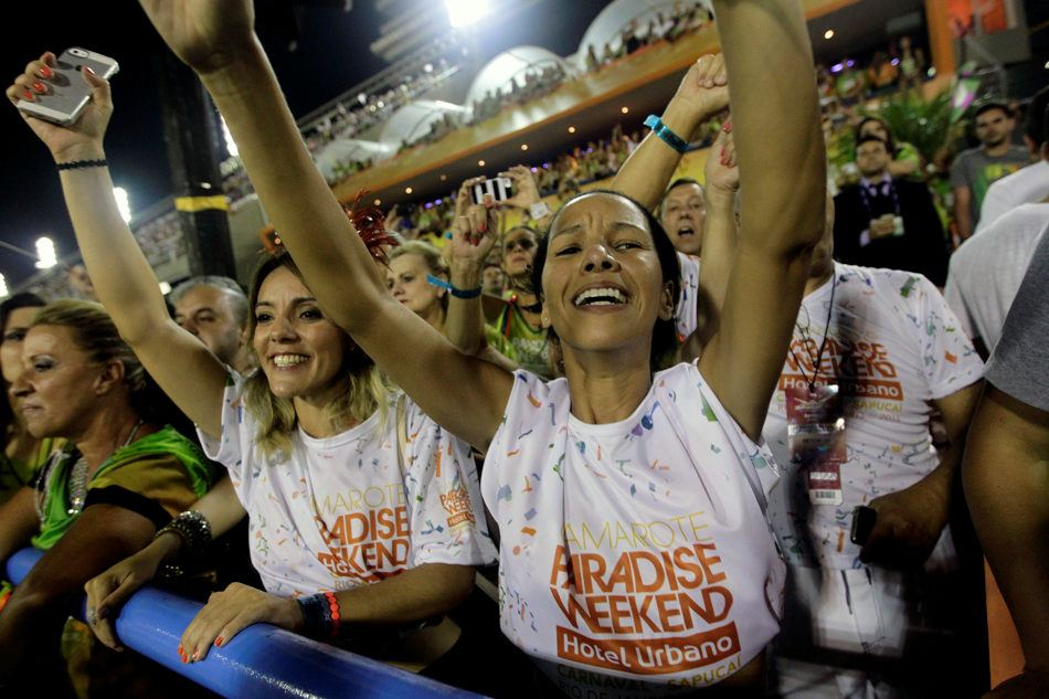People attend the Mangueira samba school parade during carnival celebrations at the Sambadrome in Rio de Janeiro, Brazil, Monday, March 3, 2014. (AP Photo/Silvia Izquierdo)