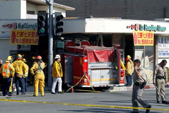 Firefighters and other officials work the scene of an accident where two firetrucks answering a call collided en route to a fire Wednesday, April 16, 2014, in Monterrey Park, Calif. The collision sent one firetruck careening into a restaurant, leaving 14 people, including several firefighters, injured. (AP Photo/Nick Ut)