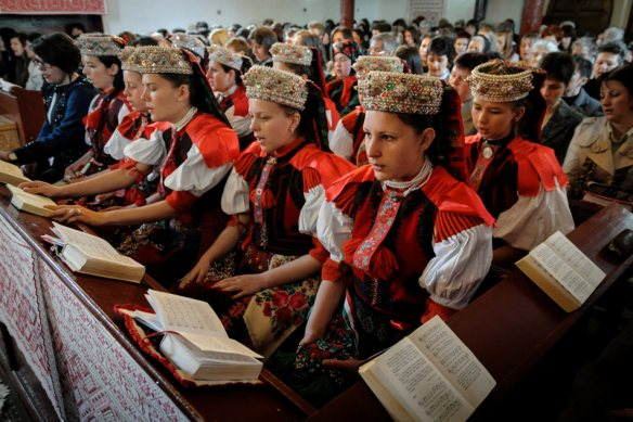 Ethnic Hungarian girls wearing traditional folk costumes attend the Easter service in the Reformed church of the village of Sancraiu, Transylvania, North Western Romania, Sunday, April 20, 2014. (AP Photo/MTI, Zsolt Czegledi)
