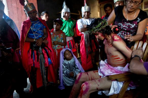 "An actor portraying Jesus holds still as his body is painted in preparation for the ""Via Crucis,"" or Stations of the Cross procession during Holy Week celebrations as fellow actors watch, in the indigenous neighborhood of Monimbo in Masaya, Nicaragua, Thursday, April 17, 2014. (AP Photo/Esteban Felix)"