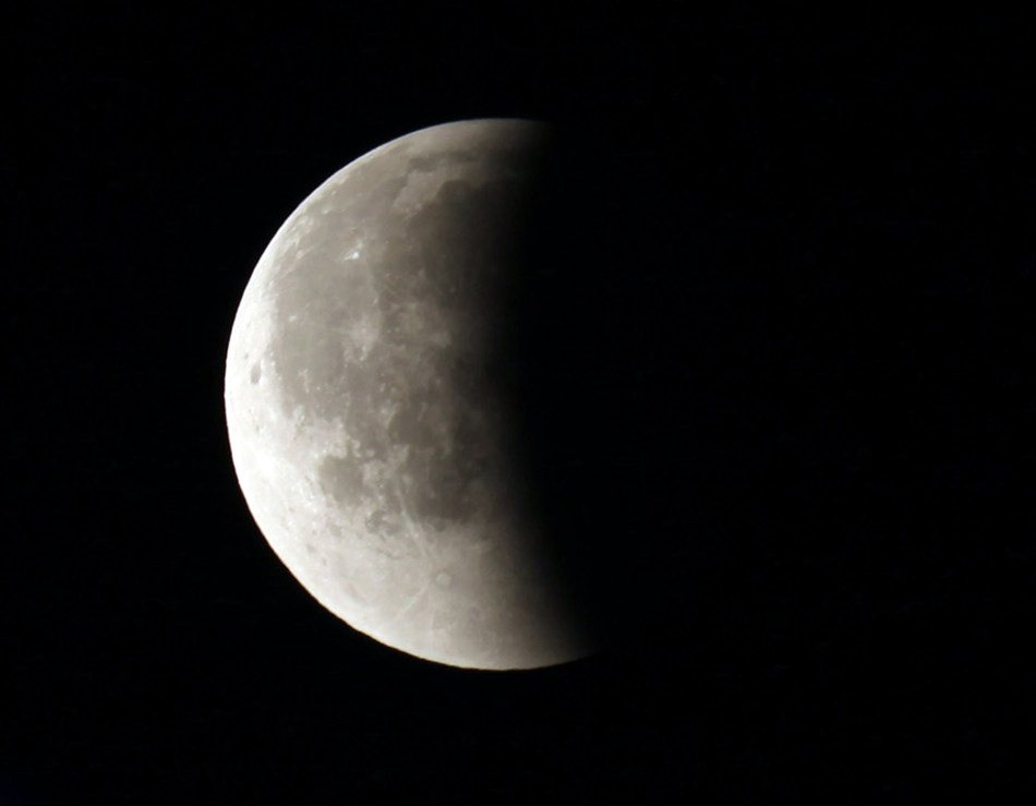 Earth's shadow partially covers the moon toward the end of a total lunar eclipse Tuesday, April 15, 2014, as seen from the Milwaukee area. Tuesday's eclipse is the first of four total lunar eclipses that will take place between 2014 to 2015. (AP Photo/Milwaukee Journal-Sentinel, Mike De Sisti)