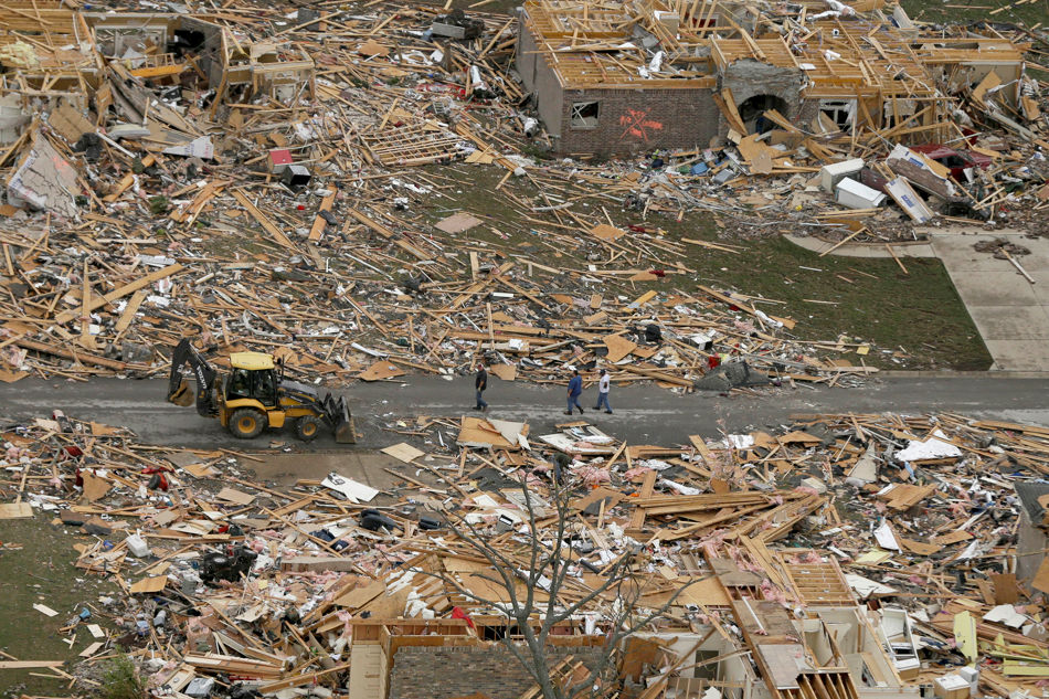 People walk between two destroyed houses in Mayflower, Ark., Monday, April 28, 2014, after a tornado struck the town late Sunday. A tornado system ripped through several states in the central U.S. and left at least 17 dead in a violent start to this year's storm season, officials said. (AP Photo/Danny Johnston)