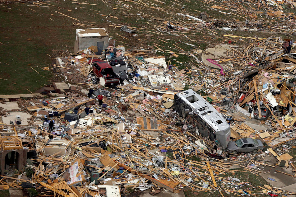 A travel trailer sits inn the rubble of a house in Mayflower, Ark., Monday, April 28, 2014, after a tornado struck the town late Sunday. A storm system ripped through several states in the central U.S. and left at least 16 dead in a violent start to this year's storm season, officials said. (AP Photo/Danny Johnston)