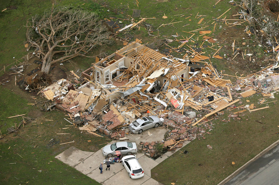 Two men stand in front of a destroyed house in Mayflower, Ark., Monday, April 28, 2014, after a tornado struck the town late Sunday. A tornado system ripped through several states in the central U.S. and left at least 17 dead in a violent start to this year's storm season, officials said. (AP Photo/Danny Johnston)