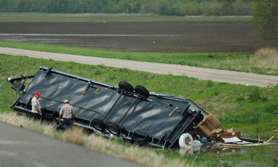 Motorists check out a travel trailer damaged in an accident involving high winds from a severe thunderstorm that passed near Rich Hill, Mo., Sunday, April 27, 2014. (AP Photo/Orlin Wagner)