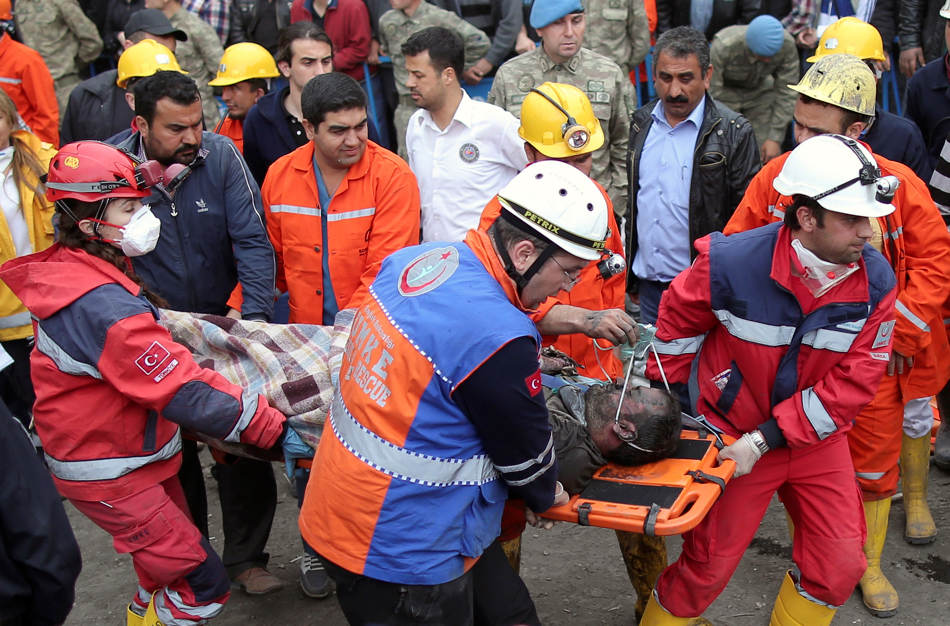 Rescue workers carry the dead body of a miner from the mine in Soma, western Turkey, early Wednesday, May 14, 2014. Rescuers desperately raced against time to reach more than 200 miners trapped underground Wednesday after an explosion and fire at a coal mine in western Turkey killed at least 200 workers, authorities said, in one of the worst mining disasters in Turkish history. Turkey's Energy Minister Taner Yildiz said 787 people were inside the coal mine in Soma, some 250 kilometers (155 miles) south of Istanbul, at the time of the accident and 363 of them had been rescued so far. (AP Photo/Emrah Gurel)