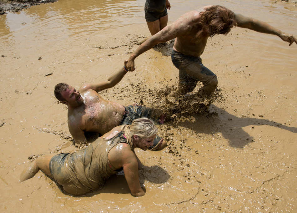 TING SHEN/JOURNAL STAR  Contestants try to pull each other up during a mud volleyball fundraising tournament Sunday, June 29 at Marshall County Sand Trap in Lacon.