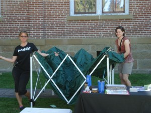 Chalk artist Cathy Gallatin and Britt Festival staff member Sara King Cole setting up some shade for the day.