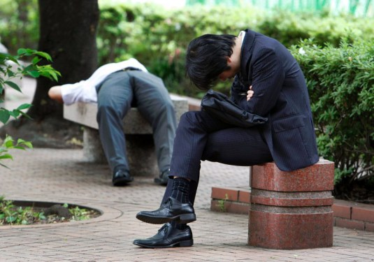 Businessman takes a rest in a park in Tokyo, Japan, Tuesday, May 17, 2011. (AP Photo/Shizuo Kambayashi)