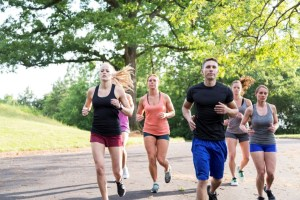 A group of six athletes jogging down a tree lined road.  One man and four women.  The man leads the group.  All are caucasian.  Outdoors, lots of green in the composition.  Motion blur.  Shot in Atlanta, Georgia.