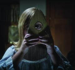 "LULU WILSON as Doris in ""Ouija: Origin of Evil.""  Inviting audiences again into the lore of the spirit board, the supernatural thriller tells a terrifying new tale as the follow-up to 2014's sleeper hit that opened at No. 1.  In 1965 Los Angeles, a widowed mother and her two daughters add a new stunt to bolster their séance scam business and unwittingly invite authentic evil into their home.  When the youngest daughter is overtaken by the merciless spirit, this small family confronts unthinkable fears to save her and send her possessor back to the other side."
