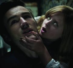 """PARKER MACK as Mikey is attacked by LULU WILSON as Doris in """"Ouija: Origin of Evil.""""  Inviting audiences again into the lore of the spirit board, the supernatural thriller tells a terrifying new tale as the follow-up to 2014's sleeper hit that opened at No. 1.  In 1965 Los Angeles, a widowed mother and her two daughters add a new stunt to bolster their séance scam business and unwittingly invite authentic evil into their home.  When the youngest daughter is overtaken by the merciless spirit, this small family confronts unthinkable fears to save her and send her possessor back to the other side."""