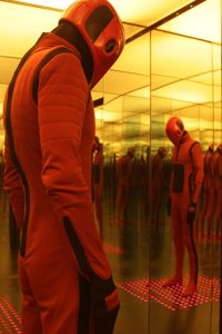 A sentionaut stands dormant in a room full of mirrors.