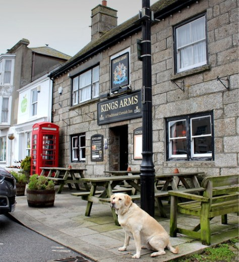 A dog sits outside the King's Arms, St Just.