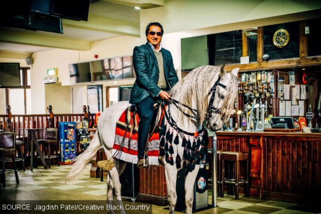 A man astride a horse in the public bar of a pub.
