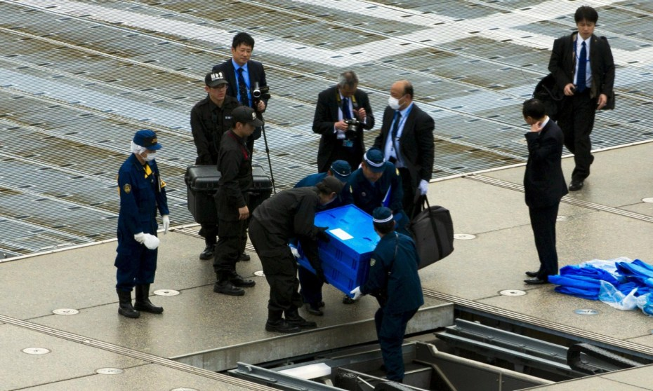 Officials carry a blue box reportedly containing a drone from the rooftop of Shinzo Abe's offices in Tokyo. Photograph: Thomas Peter/Reuters