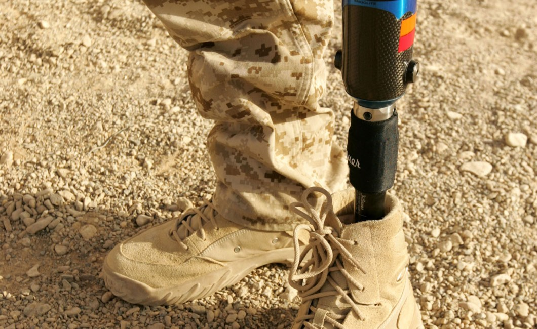 Corporal Garrett S. Jones displays one of the seven prosthetic legs he now wears after being injured in 2007 by an insurgent's bomb during his unit's deployment to Iraq.  Six of his legs are used for walking, and one is for snowboarding. (Marine Corps photo by Sgt. Ray Lewis)