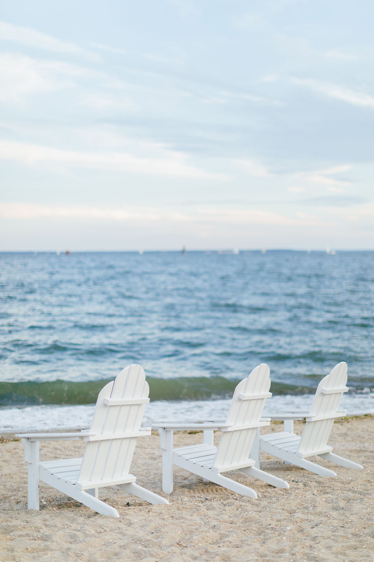 White Adirondack Chairs On The Beach With Blue Water Bows Sequins