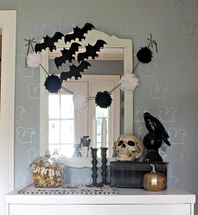 black and white halloween vignette on dresser in foyer