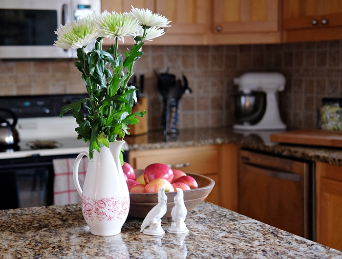 Boxy Colonial Spring Home Tour: mums and dough bowl in kitchen