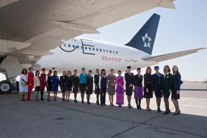 Staff representatives from Star Alliance member airlines, dressed in their official uniforms, pose beneath the wing of Ethiopian Airlines' Star Alliance liveried 767. The uniformed staff gathered in Addis Ababa for the official ceremony marking Ethiopian's joining of Star Alliance.