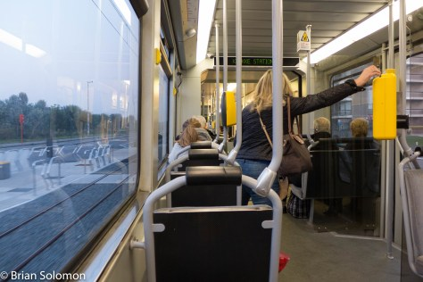 A passenger validates a ticket on-board the Kusttram.