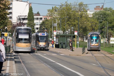 Bright sun finds three variety of Brussels trams.